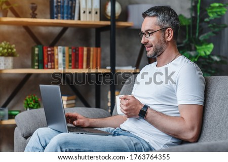 Side view of a senior man using laptop while sitting on a sofa in living room at home Stock photo © wavebreak_media