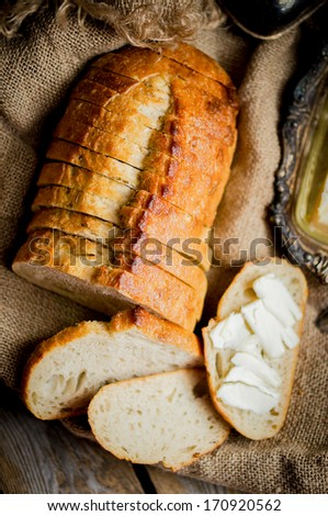 Cut of fresh loaf of white bread with flour and butter on light kitchen table background with choppi Stock photo © DenisMArt