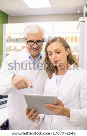 Jóvenes médicos senalando touchpad Screen mirando Foto stock © pressmaster