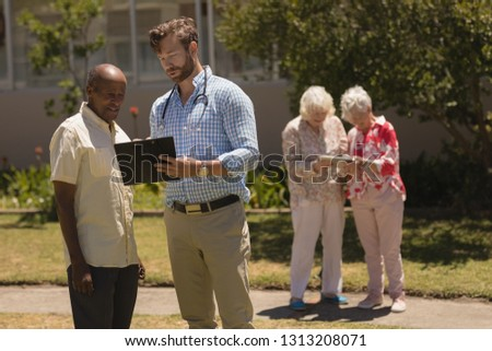 front view of male doctor interacting with senior man over clipboard while two senior women laughing stock photo © wavebreak_media
