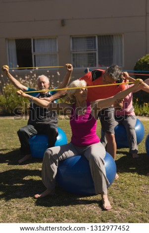 front view of trainer assisting senior women in performing exercise with elastic band and ball in th stock photo © wavebreak_media