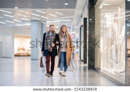 young affectionate couple in casualwear moving along shop windows in the mall stock photo © pressmaster