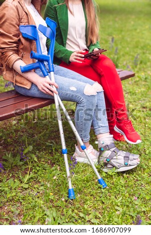 Two women, one healthy and one with a sprained foot, on a bench Stock photo © Kzenon