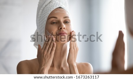 Pretty young satisfied woman applying hydrating cream on her face Stock photo © pressmaster