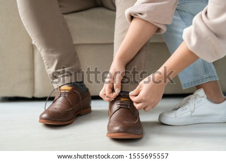 Hands of careful woman helping her sick disable father to tie shoelaces on boots Stock photo © pressmaster