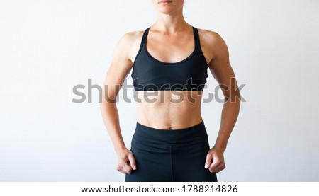 An adult woman in a beautiful muscular body against a gray wooden wall Stock photo © ElenaBatkova