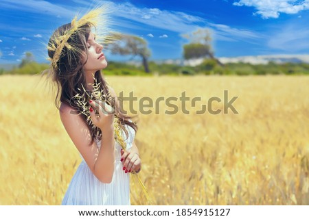 A woman in an agricultural field with a wreath on her head of red poppies Stock photo © ElenaBatkova