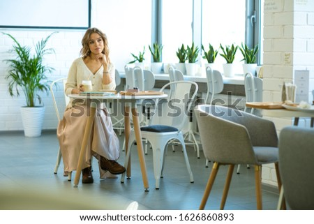 Restful young woman in smart casualwear having cappuccino with dessert Stock photo © pressmaster