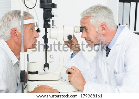 Side view of Caucasian male doctor checking senior male patient mouth with otoscope at clinic at ret Stock photo © wavebreak_media