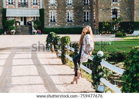 Restful female spends her free time, walks near old ancient brick castle, leans at white hence, wear Stock photo © vkstudio