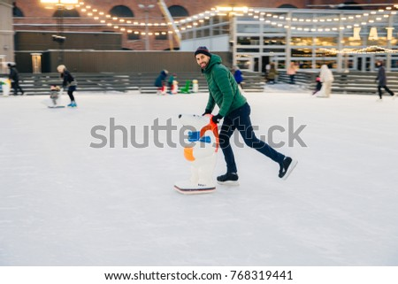 Cheerful man spends free time on skate ring, uses skate aid, lea Stock photo © vkstudio