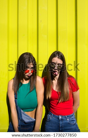Two cute casual young women fooling around in front of yellow wa Stock photo © boggy