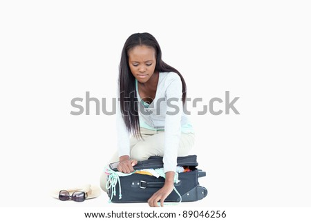 Young woman having problems closing her suitcase against a white background stock photo © wavebreak_media