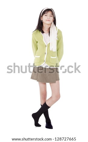 Stock photo: Unsmiling confident young girl in green sweater standing, isolat
