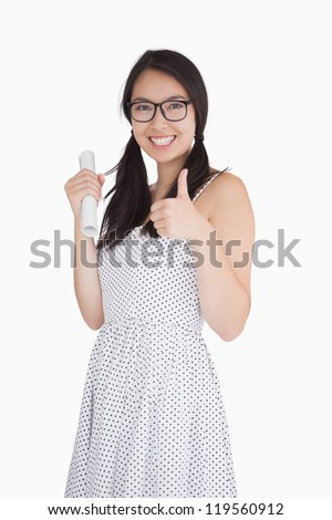 Stockfoto: Smiling Woman Giving Thumbs Up And Holding Rolled Up Piece Of Paper
