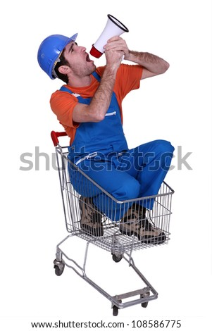 Tradesman sitting in a shopping cart and yelling into a megaphone Stock photo © photography33