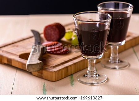 Red wine with salami and grapes on old wood table and some grape Stock photo © phila54