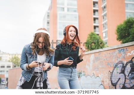 vrouwen · mp3-speler · glimlachend · technologie · stedelijke · hoofdtelefoon - stockfoto © monkey_business