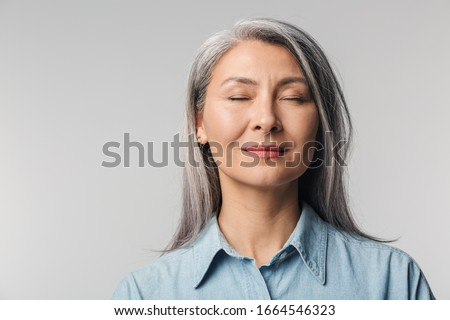 Closeup portrait of attractive woman with closed eyes over white background Stock photo © deandrobot