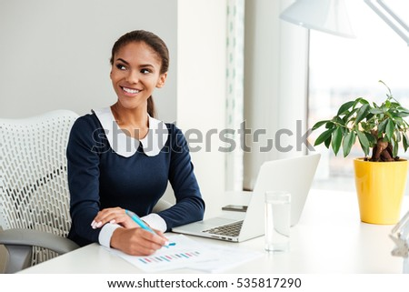 Smiling woman in black dress sitting on the office chair over gray background Stock photo © deandrobot