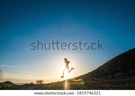 silhouette of man running on the rocky trail at sunset extreme sports stock photo © maxpro