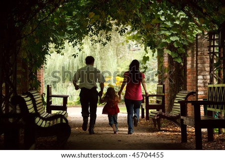 Parents and little girl in summer garden in plant tunnel. Girl plays being shaken on hands of parent Stock photo © Paha_L
