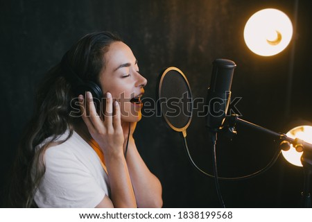 portrait of a beautiful woman singing into microphone with headphones stock photo © master1305