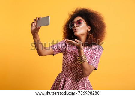 cute lovely african american woman standing and sending a kiss stock photo © deandrobot