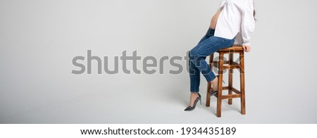 Woman with long legs sits on a wooden chair, isolated on white b Stock photo © Nobilior