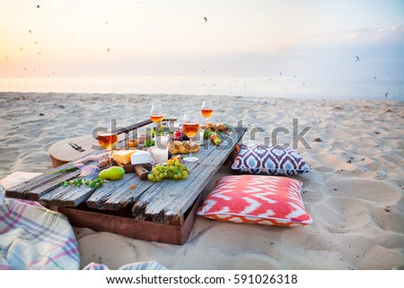 Picnic on the beach at sunset in boho style, food and drink conc Stock photo © Yatsenko