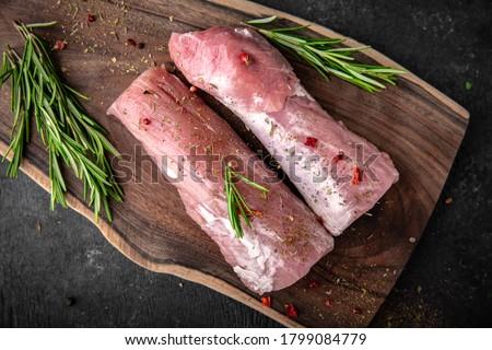 Fresh raw pork tenderloin on wooden cutting board on dark background Stock photo © yelenayemchuk