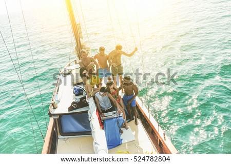 Multiracial young friends having boat party at sunset - Dj playi Stock photo © DisobeyArt