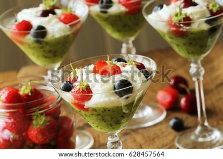 Desert with strawberry , blueberry, kiwi , cherry in glass of whipped cream Stock photo © Virgin
