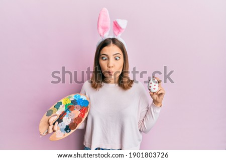 beautiful young woman with rabbit ears holding mouthful of lollipop stock photo © orensila