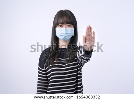 Close-up portrait of serious young asian lady showing stop gestu Stock photo © deandrobot