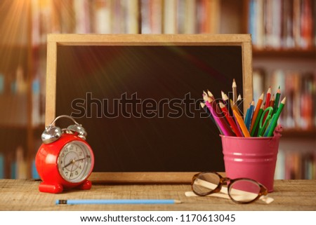 Slate with desk organizer and alarm clock by eyeglasses against library shelf Stock photo © wavebreak_media