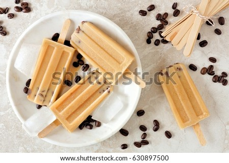 coffee and chocolate popsicles with ice on light marble background with copy space flat lay stock photo © artjazz