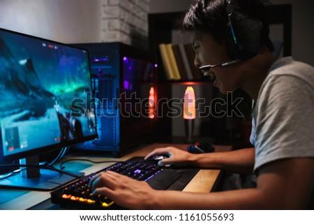 сидят · играет · компьютерная · игра · темно · комнату · концентрированный - Сток-фото © deandrobot