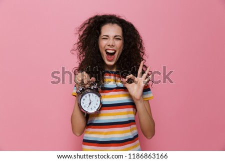 photo of european woman 20s with curly hair holding alarm clock stock photo © deandrobot