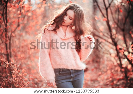 Young girl in a sweater in a color of the year 2019 Living Coral Pantone holding a bouquet of fresh  Stock photo © artjazz