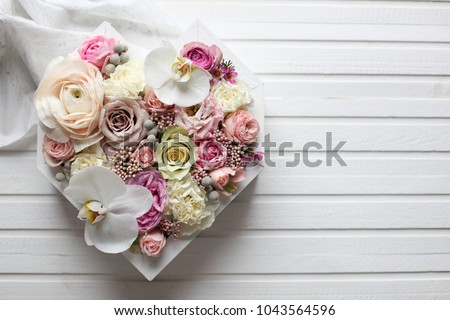 A beautiful bouquet of flowers of a Ranunculus in a girl's hands with tatoo on a gray background. Tr Stock photo © artjazz