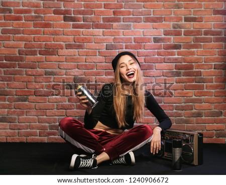 Image of european hip hop girl, sitting on floor against brick w Stock photo © deandrobot