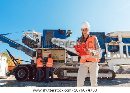 Civil Engineer woman with clipboard in front of stone crusher Stock photo © Kzenon