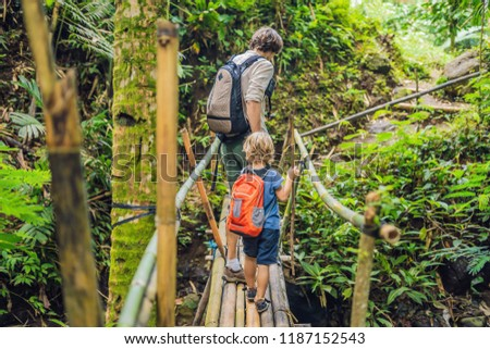 Father and son travelers on the suspension bridge in Bali. Trave Stock photo © galitskaya
