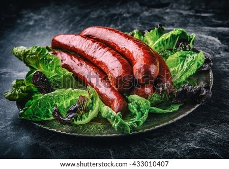 Raw beef and pork sausage on vintage chopping board with salt and pepper on black background. Stock photo © DenisMArt