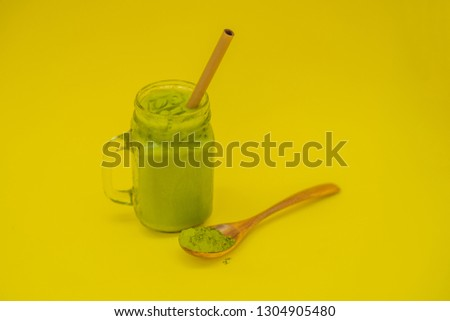 Green tea latte with ice in mason jar and straw and spoon with powder matcha on yellow background. H ストックフォト © galitskaya