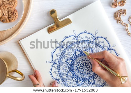 Woman is drawing on hand. Draw on the hand Indian mehendi picture Stock photo © galitskaya