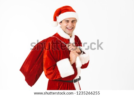 Stock photo: Portrait of optimistic man 30s in santa claus costume and red ha