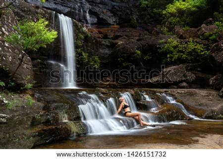 Woman sitting in flowing waterfall cascades immersed in nature oasis Stock photo © lovleah