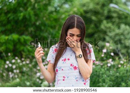Young pretty woman blowing nose in front of blooming tree. Spring allergy concept VERTICAL FORMAT fo Stock photo © galitskaya